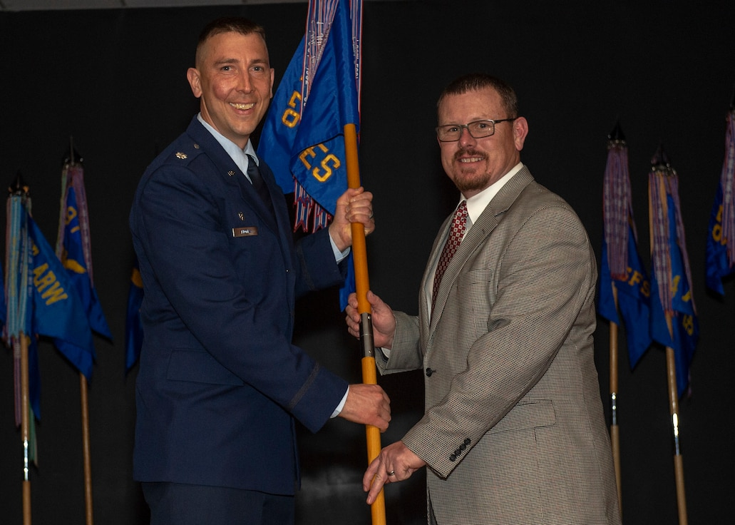 U.S. Air Force Lt. Col. Steven Thomas, 97th Civil Engineer Squadron commander, hands the 97th CES guidon to Mr. Kevin Marple, Johnny Roberts Motors director, during the Honorary Commanders Induction, March 29, 2019, at Altus Air Force Base, Okla. Inductees were called to the stage to meet with their commanders and receive a 97th Air Mobility Wing pin as a symbol of recognition. (U.S. Air Force Photo by Senior Airman Jackson N. Haddon)