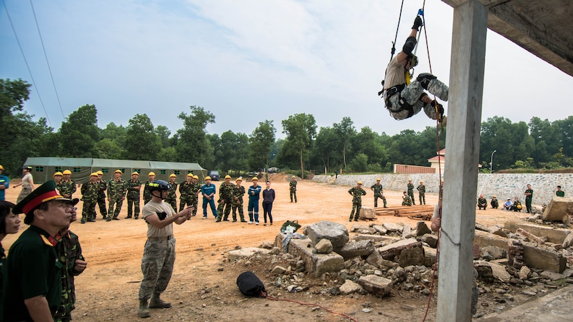 Soldier rappels as people watch.