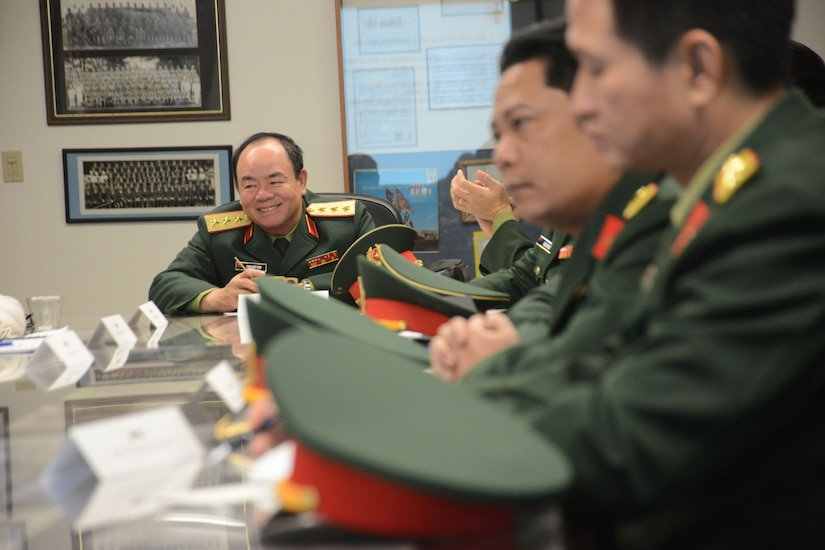 Vietnamese military personnel sit at a table.