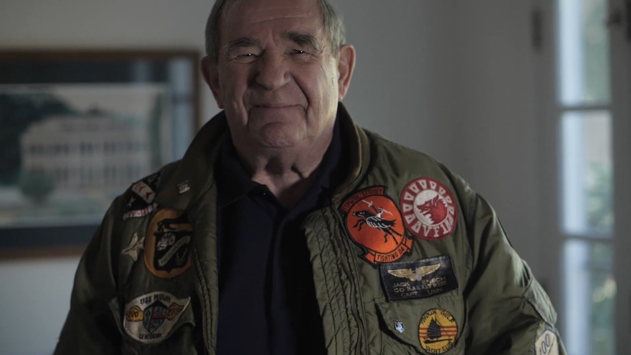 A man poses for a photo wearing a flight jacket covered in patches.