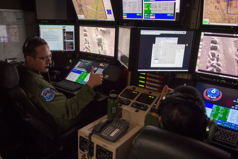 Capt. David (left), 6th Attack Squadron MQ-9 Reaper pilot, and  Tech. Sgt. Joaquin, 6th Attack Squadron MQ-9 Reaper sensor operator instructor, provide close air support over Red Rio Range, N.M., during an exercise, March 14, 2019, at the 6th Attack Squadron on Holloman Air Force Base, N.M. During the exercise, combat rescue officer students applied their training in a simulated deployed environment on Red Rio Range, N.M., by communicating with an actual MQ-9 overhead. (U.S. Air Force photo by Airman 1st Class Kindra Stewart)