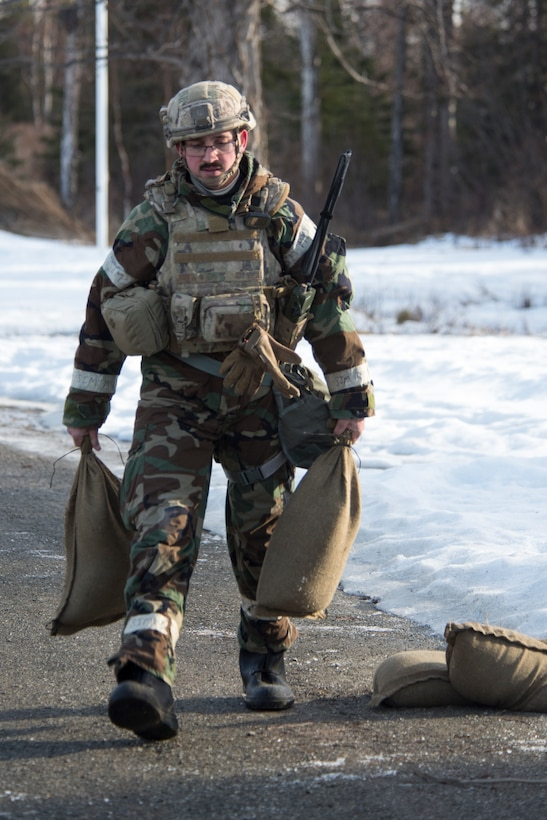 Senior Airman Rane Murphy, a 673d Civil Engineer Squadron Explosive Ordnance Disposal journeyman, carries sand bags used in a simulated chemical environment during Polar Force 19-4 at Joint Base Elmendorf-Richardson, Alaska, April 2, 2019. Polar Force is a two-week exercise designed to test JBER's mission readiness and strengthen and develop the skills service members require when facing adverse situations.