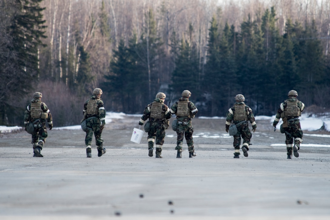 Explosive Ordnance Disposal Airmen conduct rapid clearing of submunitions on an airfield in a simulated chemical environment during Polar Force 19-4 at Joint Base Elmendorf-Richardson, Alaska, April 2, 2019. Polar Force is a two-week exercise designed to test JBER's mission readiness and strengthen and develop the skills service members require when facing adverse situations.