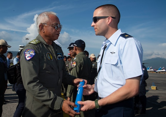 Malaysian Gen. Tan Sri Affendi Buang, Royal Malaysian Air Force chief, gives a certificate to U.S. Air Force Maj. Eric Myatt, assigned to U.S. Pacific Air Forces, Joint Base Pearl Harbor-Hickam, Hawaii, during an appreciation ceremony at the Langkawi International Maritime and Aerospace Exhibition 2019 in Padang Mat Sirat, Malaysia, March 29, 2019.