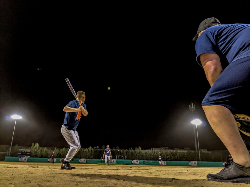 Spc. Jared Vejtruba prepares to swing the bat during an off-duty softball social event between service members of Task Force Spartan and the local Kuwaiti community on March 15, 2019 at the Hunting and Equestrian Club in Kuwait. The event brought people of all ages, nationality and gender, encouraging participation within the sport and local support for the activities. Soldiers are encouraged to develop a pathway for Community Outreach and Social Partnerships with Sporting Events as part of Every Soldier's an Ambassador program.