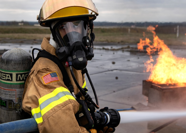 Omar Moylan, a senior at Spangdahlem High School, looks back to his partner for guidance during a live-fire simulated aircraft burn exercise at Spangdahlem Air Base, Germany, March 26, 2019. The exercise was Moylan's first experience extinguishing a live fire. He has been training with the 52nd Civil Engineer Squadron Fire Department for two months and plans to continue until he graduates. (U.S. Air Force photo by Airman 1st Class Valerie Seelye)