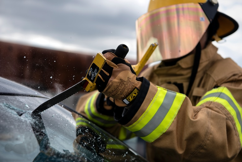 Omar Moylan, a senior at Spangdahlem High School, cuts through a windshield at Spangdahlem Air Base, Germany, March 26, 2019. Moylan, who plans on becoming a firefighter, participated in vehicle extrication training with the 52nd Civil Engineer Squadron Fire Department to gain real-life experience in his desired career field. (U.S. Air Force photo by Airman 1st Class Valerie Seelye)