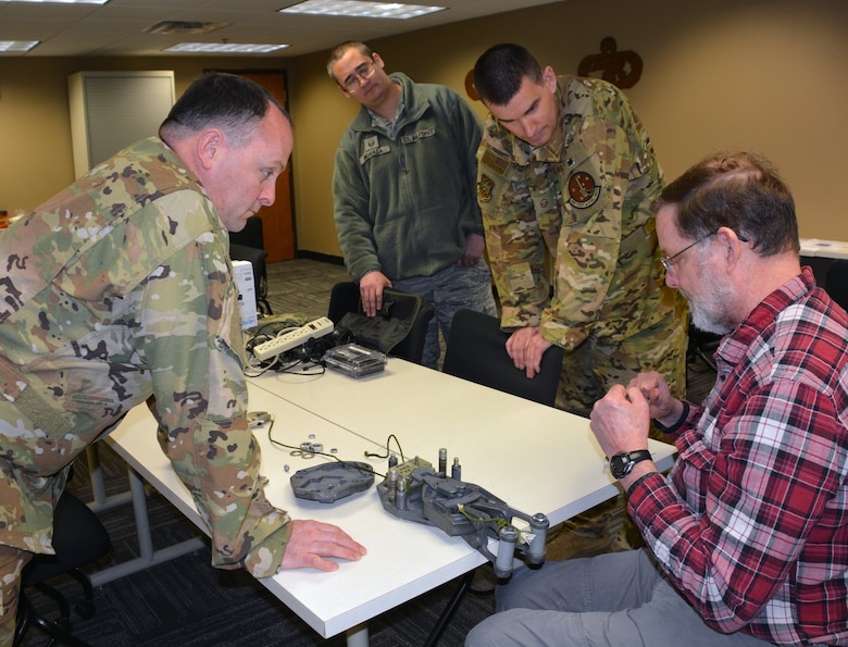 AMC Test and Evaluation Test Directors Mr. James Bonn, Master Sergeant William Gilmer, Master Sergeant Robert Morada, and Technical Sergeant Wesley Lankford inspect the 2019 AMC Spark Tank winning innovation, the M-1 Timer Block Fail-Safe Mechanism following airdrop testing at Little Rock Air Force Base, AR in February 2019. (U.S. Air Force photo by Visual Information Specialist Lisa Elmo-Henske)