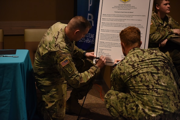 U.S. Army Maj. Shawn Lynch, 344th Military Intelligence Battalion executive officer, and Lt. Cmdr. J. Austin Maxwell, Navy Center for Information and Warfare Training Detachment, sign the proclamation outlining the observances that will be held in April at the Western Winds Dining Facility on Goodfellow Air Force Base, Texas, April 3, 2019. There will be events around base throughout the month of April in support of the observances. (U.S. Air Force photo by Senior Airman Seraiah Hines/Released)