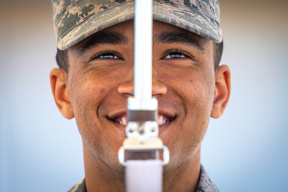 An Air Force honor guard member, shown in closeup, smiles while holding a weapon in front of the center of his face.