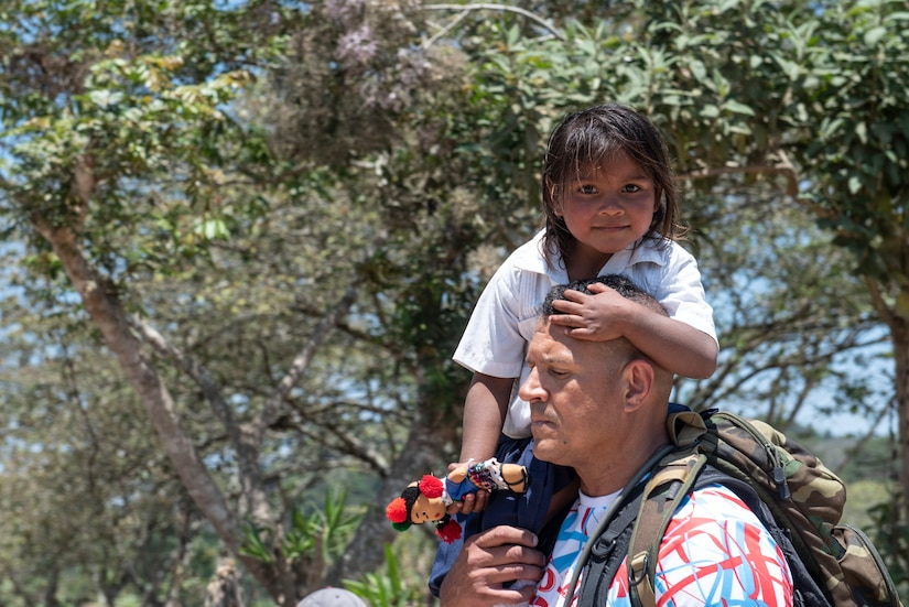 U.S. Army Lt. Col. Alex Duran, J3 Joint Operations Director, helps one of the local children on the trip down the mountain during Chapel Hike 78 in La Paz, Honduras, March 30, 2019.