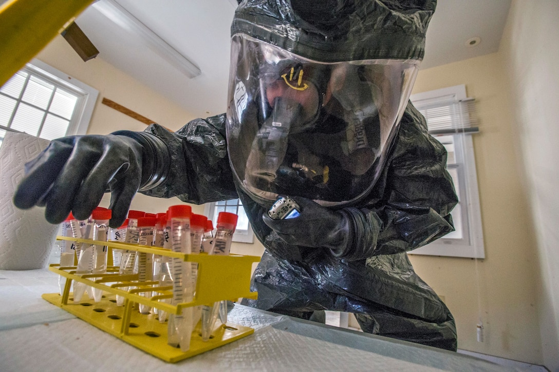 A man in a protective suit inspects vials.