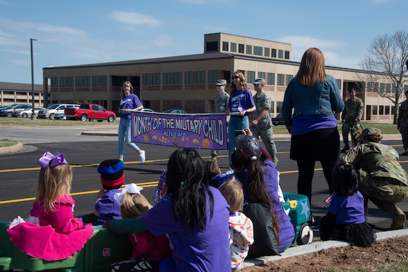 Members of the 97th Air Mobility Wing youth center watch the front of the Month of the Military Child parade, April 1, 2019, at Altus Air Force Base, Okla. After the parade passed by, the members joined in to walk with the rest of the agencies supporting the event. (U.S. Air Force photo by Senior Airman Cody Dowell)