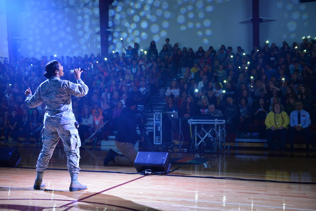 An Airman sings to an audience of high school students during an Air Force recruiting event.
