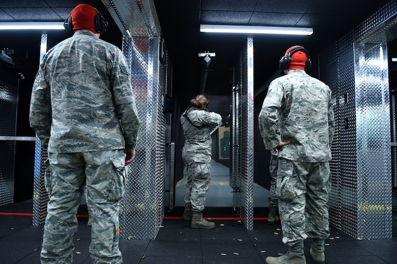 Combat arms training maintenance instructors assigned to the 180th Fighter Wing security forces squadron, Ohio Air National Guard observe as an Airman shoot during the first weapons qualification class in the new Modular Small Arms Range in Swanton, Ohio, Nov. 30, 2018. The high-tech facility is climate-controlled, has high efficiency air handlers, bullet traps and multiple simulation options that promotes safety, while providing scenario-based shooting situations for personnel to train and meet readiness requirements. (Air National Guard Photo by Senior Airman Hope Geiger)