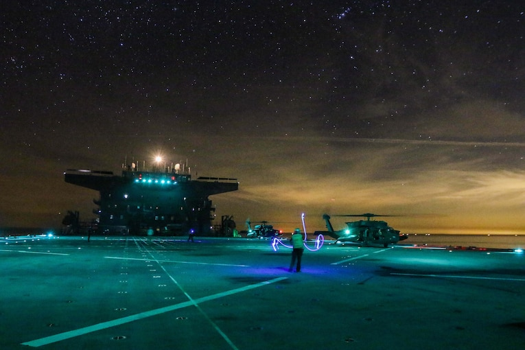 Soldiers practice landing helicopters on the deck of a ship at night.