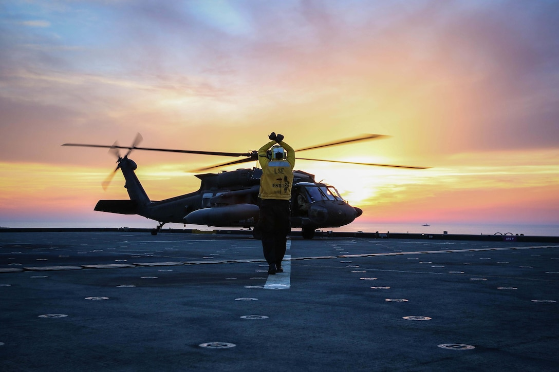 A sailor signals an aircrew in a helicopter on a military ship at twilight.