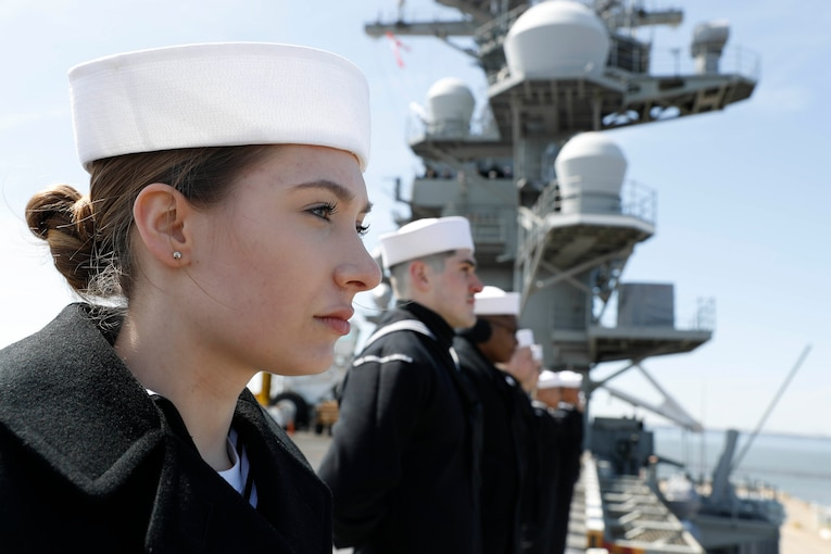Sailors man the rails of a ship.