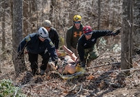 First responders carry a litter containing a dummy during a simulated wide area rescue operation held March 30-31, 2019, at the Hobet All Hazards Training Facility in Julian, W.Va. This training marked the first course to be offered at the Hobet All Hazards Training Facility. (West Virginia National Guard photo by Bo Wriston)
