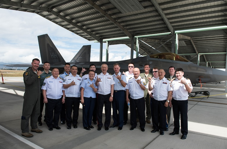 Airmen from the Mongolian Air Force Command and Pacific Air Forces take a group photo in front of a Hawaii Air National Guard F-22 Raptor during a tour around Joint Base Pearl Harbor-Hickam, Hawaii, March 26, 2019.