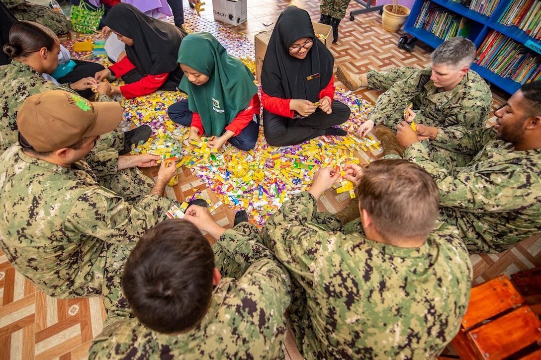 A group of sailors sit in a half circle in  front of three students with cardboard pieces between.