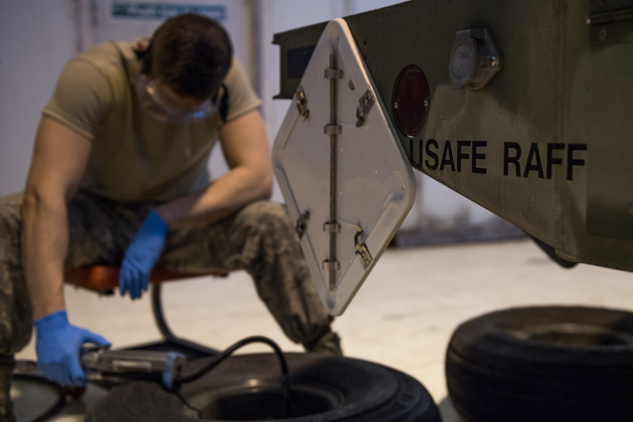 Airman 1st Class Carson Rinaldi, 2nd Munitions Squadron conventional maintenance crew chief, inflates a tire for a MHU-110 munitions trailer at RAF Fairford, England, April 2, 2019. These trailers are used to transport munitions to aircraft. (U.S. Air Force photo by Airman 1st Class Tessa B. Corrick)