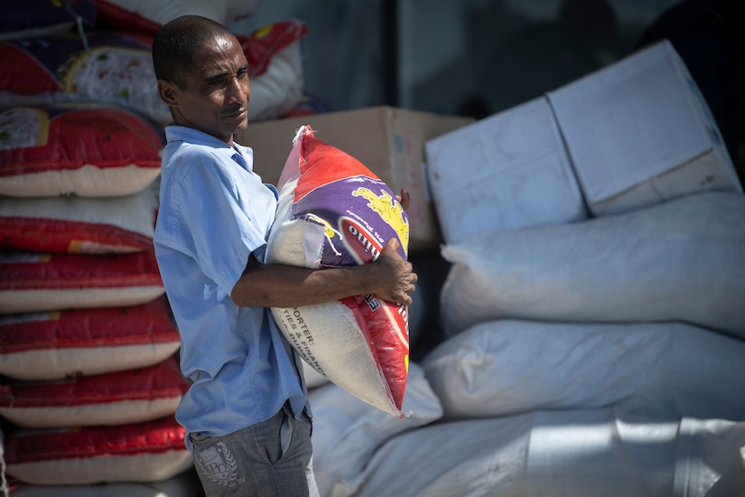 An aid worker carries a bag of food