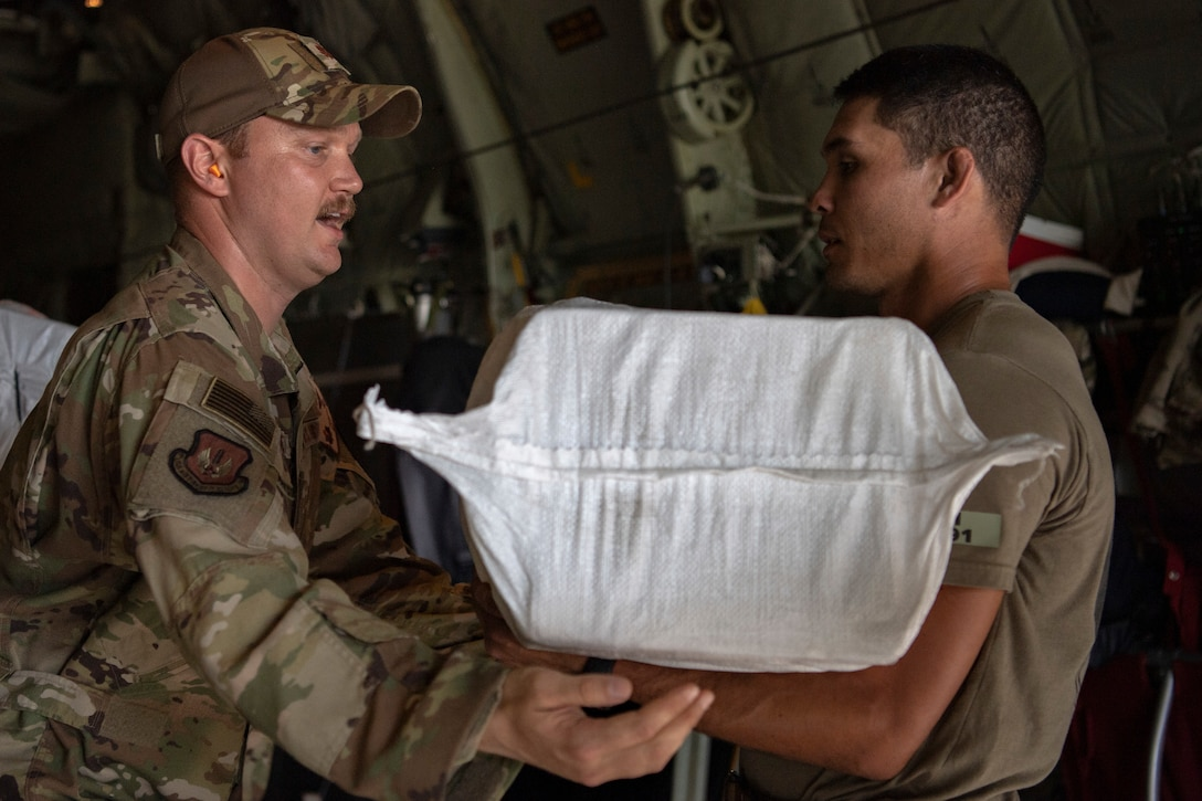 Airmen load bags of food onto an airplane
