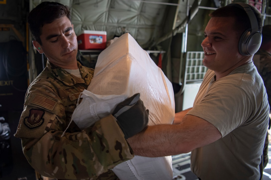 Airmen load food onto and airplane