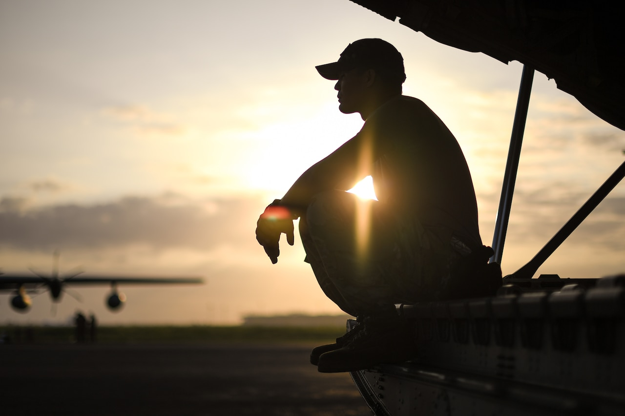 An airman rests on the ramp of an airplane.