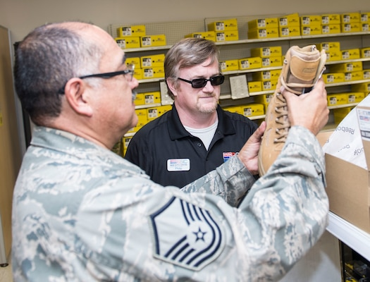 Philip Myers, 502nd Logistics Readiness Squadron Base Supply Center cashier, helps a customer with a pair of boots March 26, 2019, Joint Base San Antonio-Lackland, Texas.