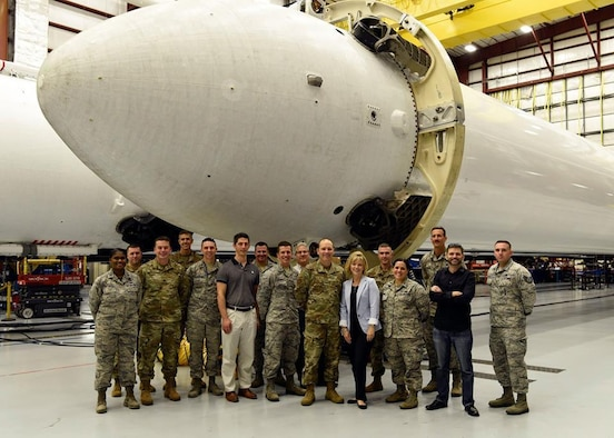 Brig Gen Douglas Schiess, 45th Space Wing commander, and his wife Debbie, pose with Airmen from the 5th Space Launch Squadron in front of SpaceX's Falcon Heavy boosters on March 22, 2019, at Kennedy Space Center, Fla. Schiess and his wife took a tour of the hangar housing the Falcon Heavy rocket while on an immersion of the 5th SLS. (U.S. Air Force photo by Airman 1st Class Zoe Thacker)