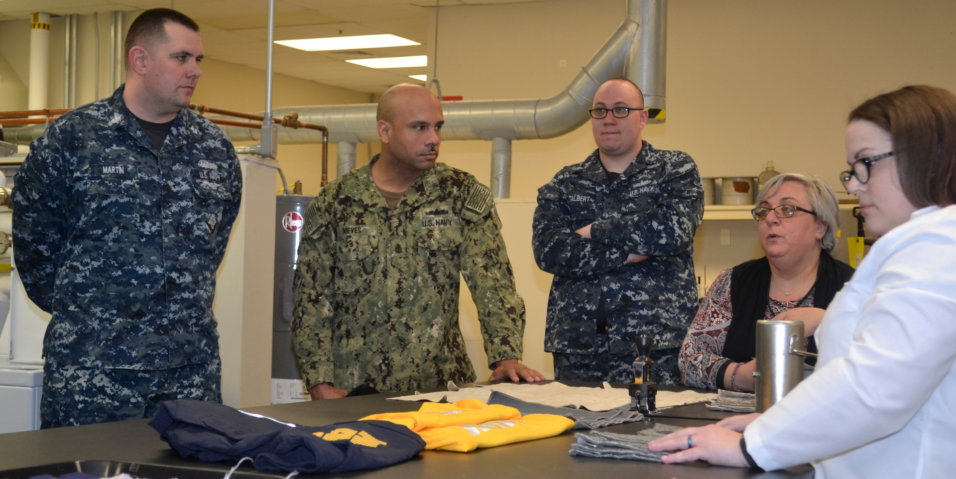 DLA Troop Support Product Test Center Analytical textile technologist Anna Wilson, far left, and lab supervisor Jamie Hieber, second from right, explain how the PTC-A testing processes aided in better adherence of reflective lettering on Navy physical training uniforms to a group of sailors assigned to Naval Support Activity Philadelphia April 3, 2019 in Philadelphia.
