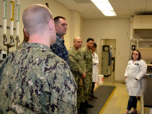 Sailors assigned to Naval Support Activity Philadelphia ask DLA Troop Support Product Test Center Analytical textile technologist Anna Wilson, far right, questions about how to properly care for their uniforms in order to maintain their non-reflective properties to remain battle-ready April 3, 2019 in Philadelphia.