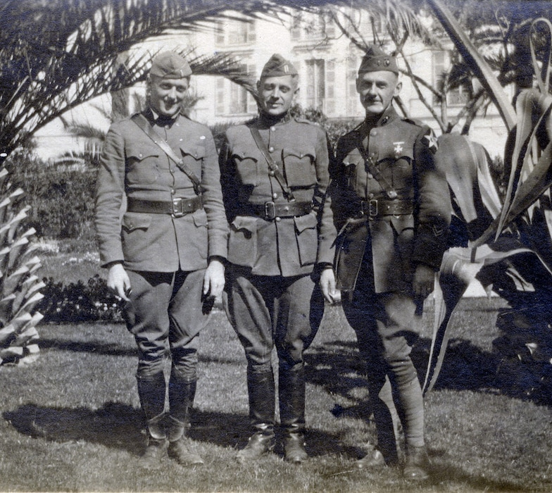 Two soldiers and one marine in hotel garden with palm trees