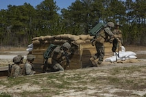 U.S. Marines with 2nd Combat Engineer Battalion (2nd CEB), 2nd Marine Division, rush out of an objective while conducting breaches with Anti-Personnel Obstacle Breaching System (APOBS) during 2nd CEB Field Exercise 2 on Camp Lejeune, North Carolina, March 27, 2019. APOBS allow safe maneuvers through fields with potential land mines to ensure mission readiness and combat effectiveness. (U.S. Marine Corps photo by Lance Cpl. Nathaniel Q. Hamilton)