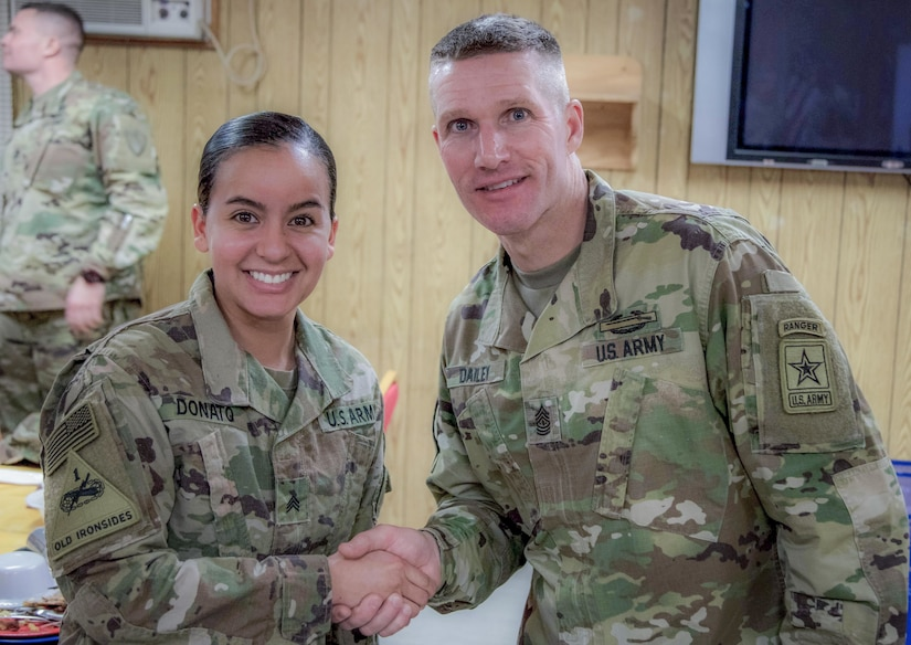Sgt. Von Marie Donato, a public affairs non-commissioned officer assigned to Combined Joint Forces Land Component Command – Operation Inherent Resolve and 1st Armored Division, shakes hands with Sergeant Maj. of the Army Daniel A. Dailey, during his visit to Baghdad, Iraq, Dec. 18, 2017, to discuss leader development initiatives, talk to the troops and enjoy a holiday meal with Soldiers.