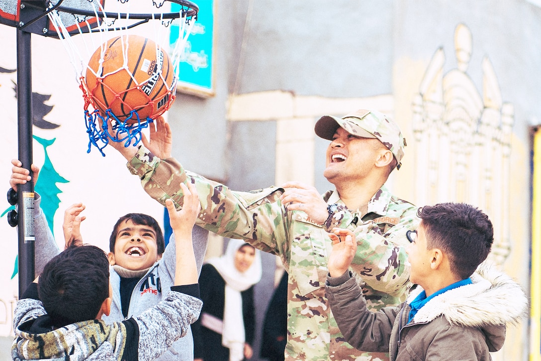 An Airman plays basketball with children.