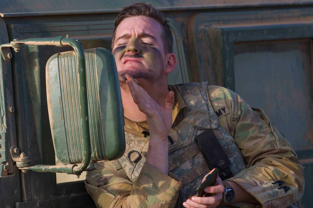 A soldier looks into the side mirror of a vehicle while applying paint to his face.