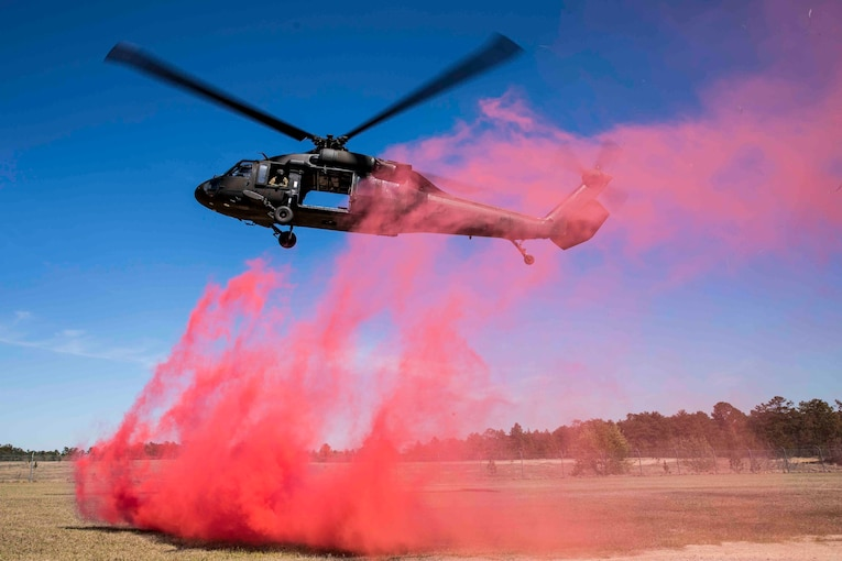 A helicopter preparing to land with pink smoke coming off the ground.