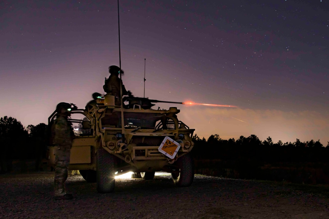 Soldiers fire a machine gun from a vehicle at night.
