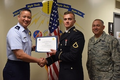 U.S. Air Force Lt. Col. Abraham Salomon, 17th Training Group vice commander, presents the 312th Training Squadron Student of the Month award to Pfc. Kamil Czerwonka, 312th TRS student, at the Brandenburg Hall on Goodfellow Air Force Base, Texas, April 5, 2019. The 312th TRS's mission is to provide Department of Defense and international customers with mission ready fire protection and special instruments graduates and provide mission support for the Air Force Technical Applications Center. (U.S. Air Force photo by Senior Airman Seraiah Hines/Released)