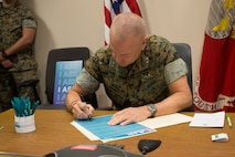 Maj. Gen. Michael F. Fahey III signs a proclamation for sexual assault awareness month at U.S. Marine Corps Forces, South, Doral, Fla., April 2, 2019.