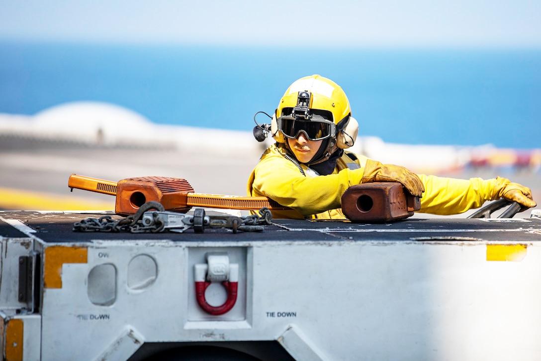 A sailor drives a tractor on a flight deck.