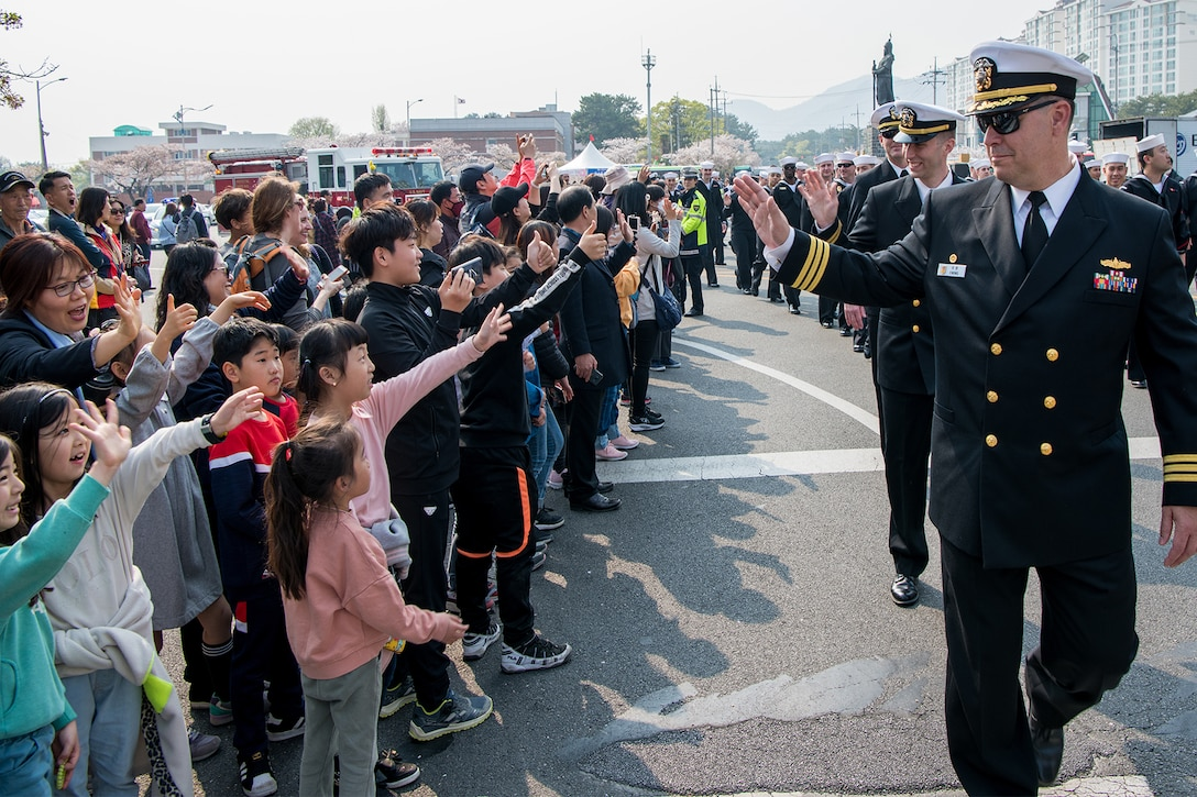 A sailor waves to children.