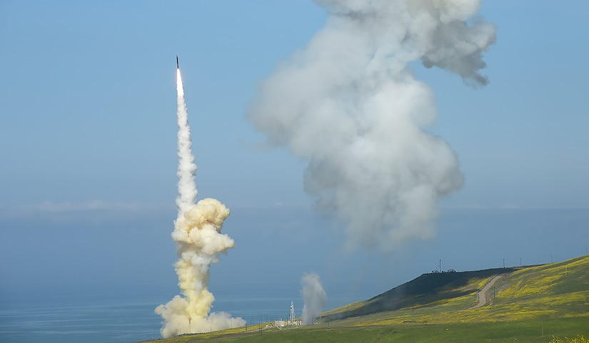 A missile launches as a cloud of smoke lingers in the sky.