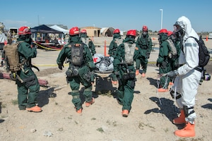 Airmen in Chem gear carrying a victim on a stretcher during an exercise