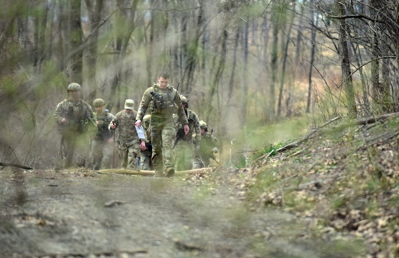 Airmen of the 148th Air Support Operations Squadron, 193rd Special Operations Wing, walk through the woods during a Tactical Combat Casualty Care field training exercise April 6, 2019, at Fort Indiantown Gap, Annville, Pennsylvania. Airmen participating in the FTX were separated into groups differentiating between being positioned with vehicles as well as on foot. (U.S. Air National Guard photo by Staff Sgt. Rachel Loftis)