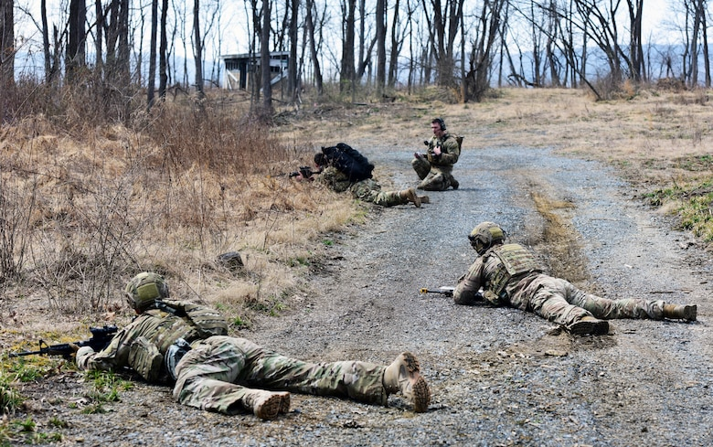 """Airmen of the 148th Air Support Operations Squadron, 193rd Special Operations Wing, lay on the ground to take cover from simulated enemy fire during a Tactical Combat Casualty Care field training exercise April 6, 2019, at Fort Indiantown Gap, Annville, Pennsylvania. Airmen participating in the FTX completed three different timed scenarios in which they moved tactically through a series of unpredicted """"ambushes"""" to provide simulated medical care for casualties. (U.S. Air National Guard photo by Staff Sgt. Rachel Loftis)"""