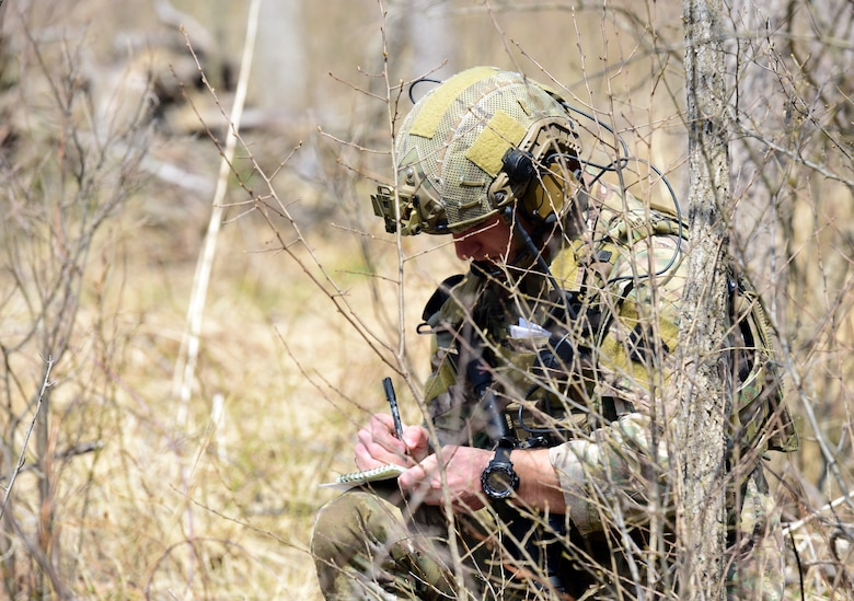 A joint terminal attack controller Airman with the 148th Air Support Operations Squadron, Fort Indiantown Gap, Annville, Pennsylvania, writes down information during a Tactical Combat Casualty Care field training exercise April 6, 2019, at the fort. The Airman maintained a low profile while relaying and receiving important information that was pertinent for the success of the FTX. (U.S. Air National Guard photo by Staff Sgt. Rachel Loftis)